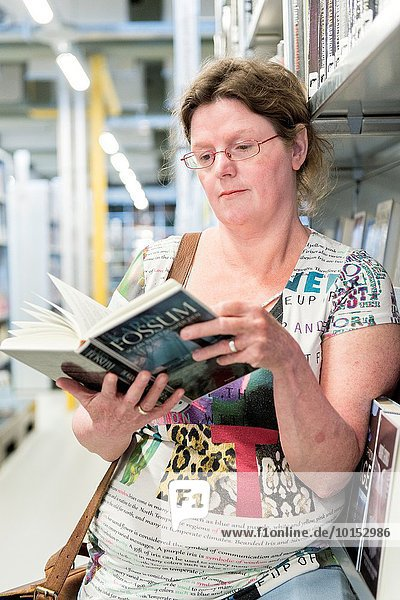 Gouda  Netherlands. Middle aged woman choosing a book to read from the library shelves.
