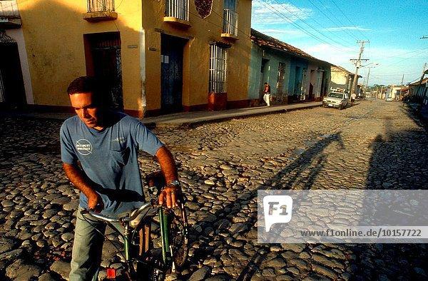 Städtisches Motiv Städtische Motive Straßenszene Mann Mensch Menschen Gebäude Straße bunt Westindische Inseln Mittelamerika Fahrrad Rad Trinidad und Tobago Kuba