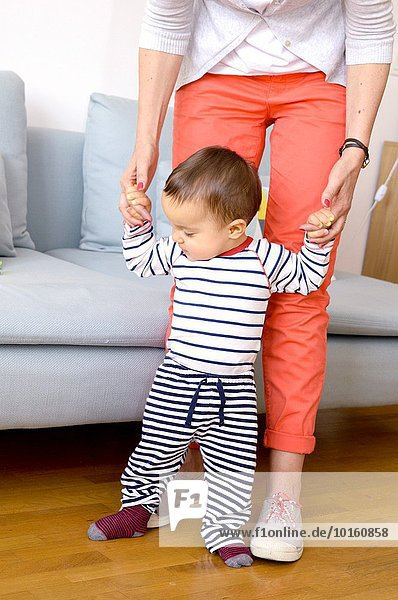 One year old baby trying to learn walking with his mother.