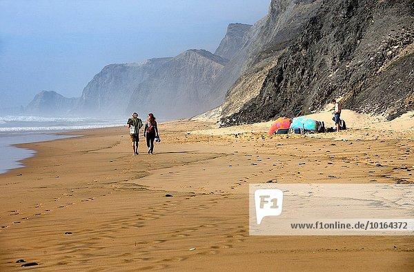 Young people on almost empty beach  Praia da Cordoama  Cordoama beach  near Vila Do Bispo  close to Sagres  Parque Natural do Sudoeste Alentejano e Costa Vicentina  South West Alentejo and Vicentine Coast Natural Park  Western Algarve  Portugal.