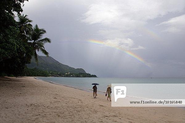 Zwei Menschen zu Fuß unter einem Regenbogen  am Indischen Ozean  Mahé  Seychellen  Afrika