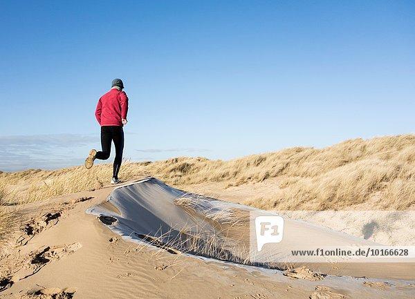 Mann Strand Großbritannien joggen Düne Frost