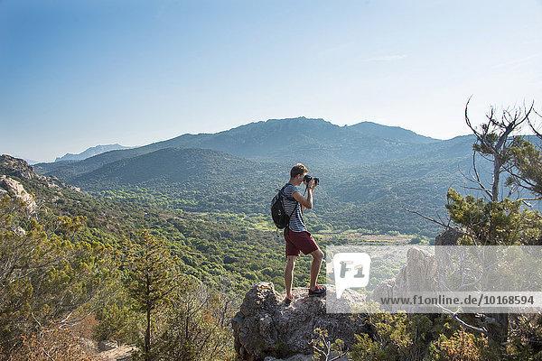 Junger Mann fotografiert bergige Landschaft bei Sartène  Korsika  Frankreich  Europa