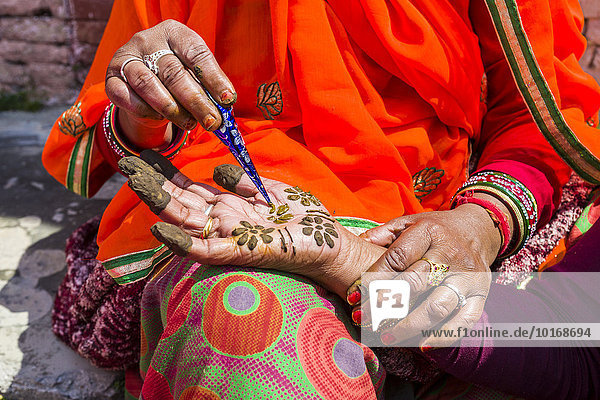 Eine indische Frau bemalt eine Hand mit Henna  vor dem Badrinath-Tempel  Char Dham Pilgerort  Badrinath  Uttarakhand  Indien  Asien