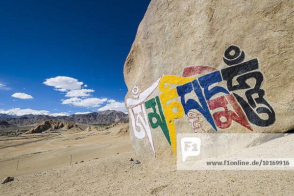 'Großer tibetischer Mani-Stein mit dem Mantra ''Om Mani Padme Hum''  in bunter Inschrift auf einem Hügel über dem Indus-Tal  Shey  Jammu und Kaschmir  Indien  Asien'