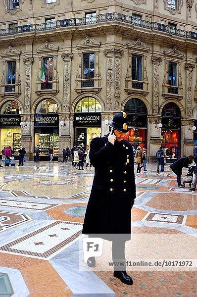 Polizist im Abendkleid mit seinem Handy in Galleria Vittorio Emanuele II  Mailand  Italien.