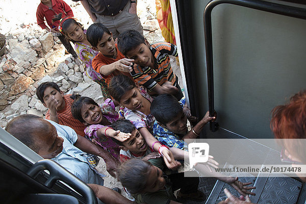 Children begging at a tourist bus  Udaipur  Rajasthan  India  Asia