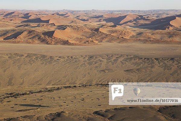 Heißluftballon über einem Trockengebiet und dem ausgetrockneten Flussbett des Tsauchab Trockenflusses am Rande der Namib-Wüste  Luftbild aus einem zweiten Ballon  Namib-Naukluft-Nationalpark  Namibia  Afrika