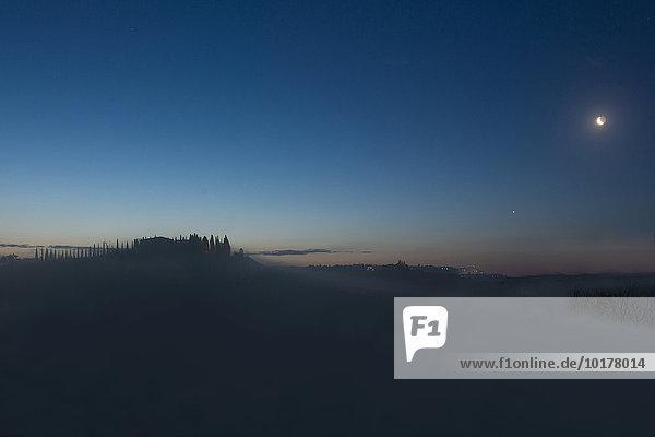 Silhouette altes Haus und Zypressen bei Sonnenaufgang im Nebel  Val d'Orcia  Toskana  Italien  Europa
