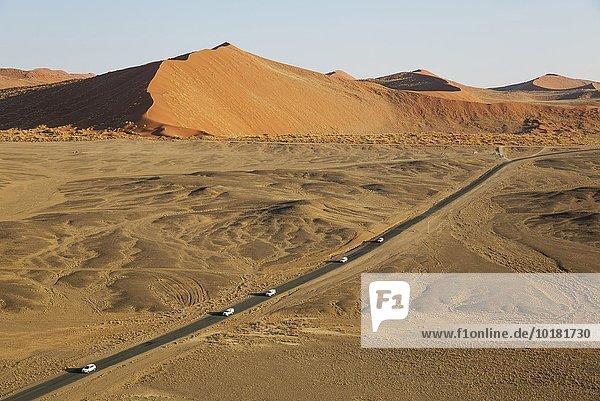 Luftbild  die asphaltierte Straße von Sesriem zum berühmten Sossusvlei im Herzen der Namib-Wüste verläuft zwischen spektakulären Sanddünen  Namib-Naukluft-Nationalpark  Namibia  Afrika