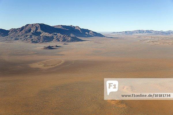Luftbild aus einem Heißluftballon  Wüstenebenen mit sogenannten Feenkreisen und isolierten Bergrücken am Rande der Namib-Wüste  NamibRand-Naturreservat  Namibia  Afrika