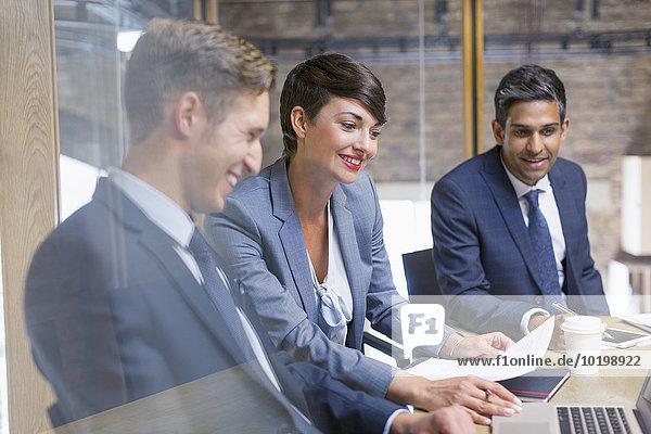 Geschäftsleute  die den Papierkram bei der Besprechung überprüfen.