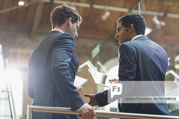 Geschäftsleute mit digitalem Tablett sprechen im Büro