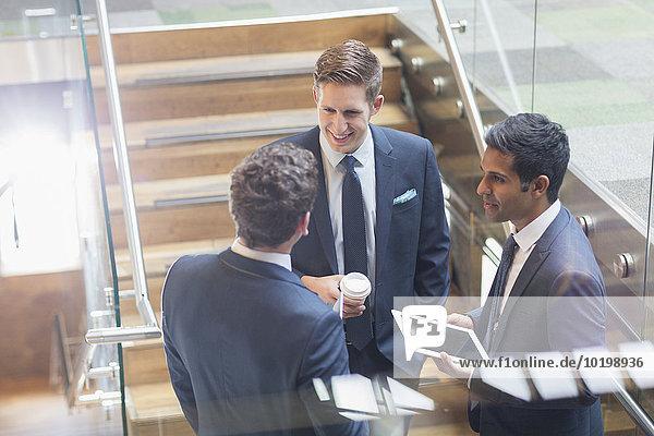 Geschäftsleute mit digitalem Tablett und Kaffee im Gespräch auf der Treppe
