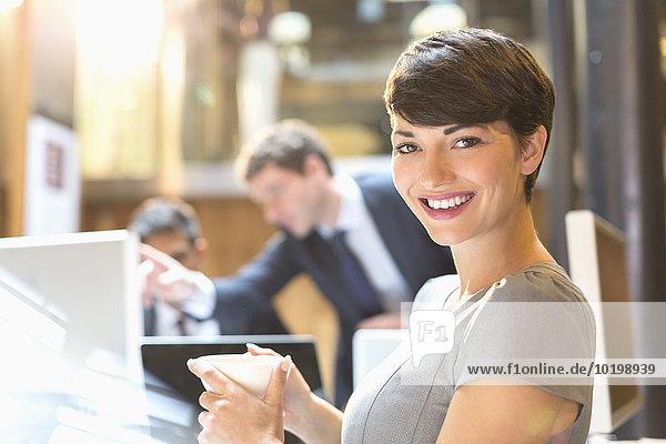 Portrait selbstbewusste Geschäftsfrau beim Kaffeetrinken im Büro