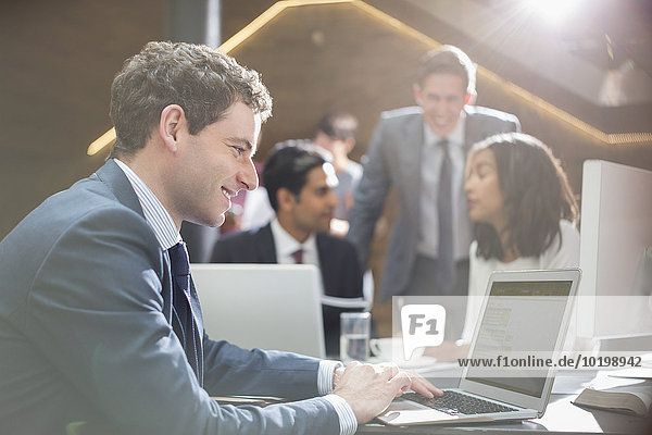 Lächelnder Geschäftsmann bei der Arbeit am Laptop im Büro