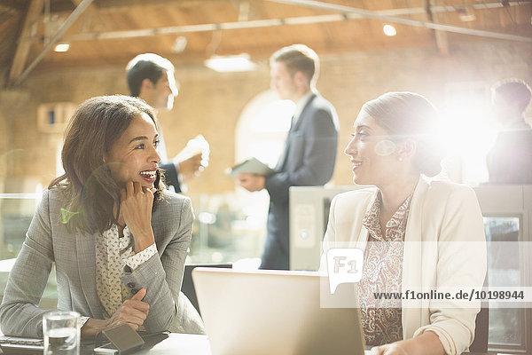 Geschäftsfrauen beim Reden und Arbeiten am Laptop im Büro
