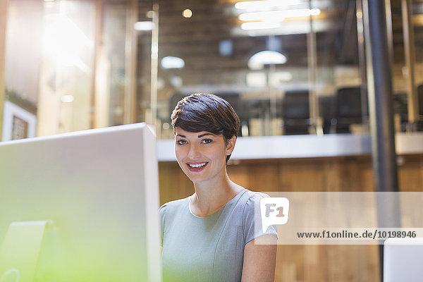 Portrait lächelnde Geschäftsfrau bei der Arbeit am Computer im Büro