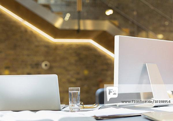 Laptop und Computer auf dem Schreibtisch mit Wasserglas und Papierkram