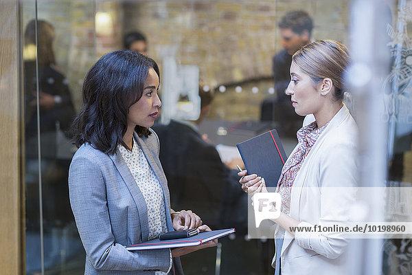 Geschäftsfrauen im Gespräch vor der Konferenzraumbesprechung