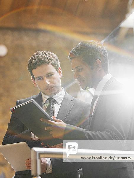 Geschäftsleute, die im Büro mit digitalen Tabletts arbeiten