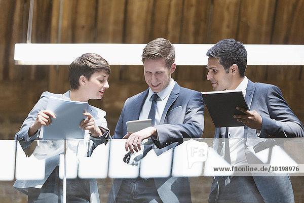 Geschäftsleute mit digitalem Tablett auf dem Bürobalkon