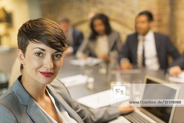 Portrait selbstbewusste Geschäftsfrau mit Laptop im Meeting