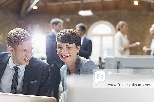 Lächelnde Geschäftsleute arbeiten am Laptop im Büro