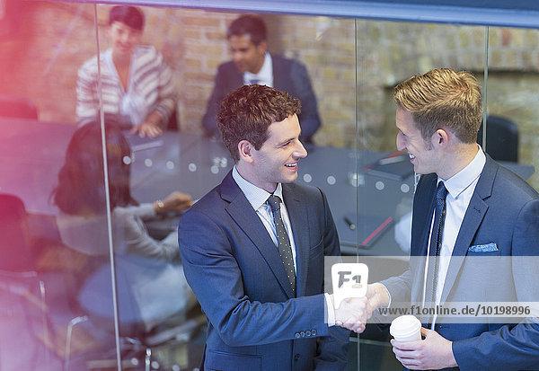 Geschäftsleute beim Händeschütteln vor der Konferenzraumbesprechung