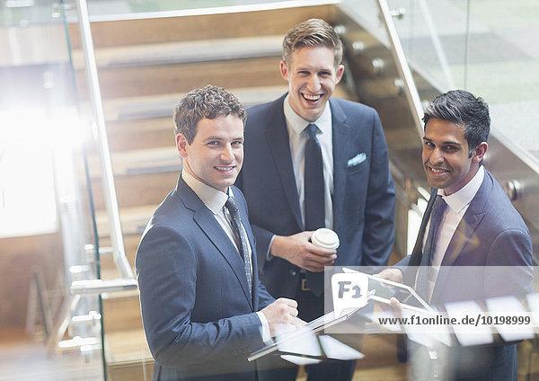 Portrait selbstbewusste Geschäftsleute mit Kaffee und digitalem Tablett auf der Treppe