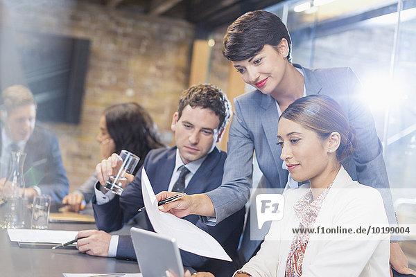 Geschäftsleute mit Papierkram und digitalem Tablett im Konferenzraum