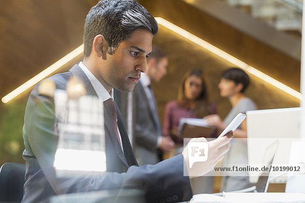 Seriöser Geschäftsmann SMS mit Handy im Büro