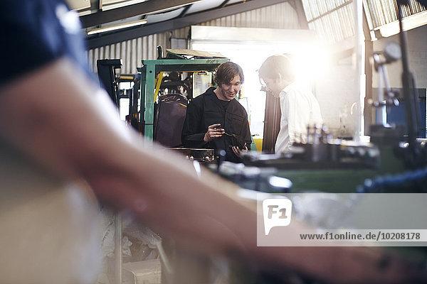 Mechaniker- und Kundengespräche in der Kfz-Werkstatt