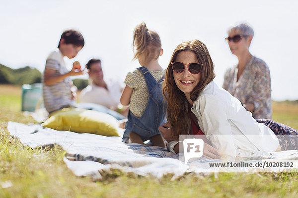 Portrait lächelnde Frau auf Decke im sonnigen Feld mit Familie