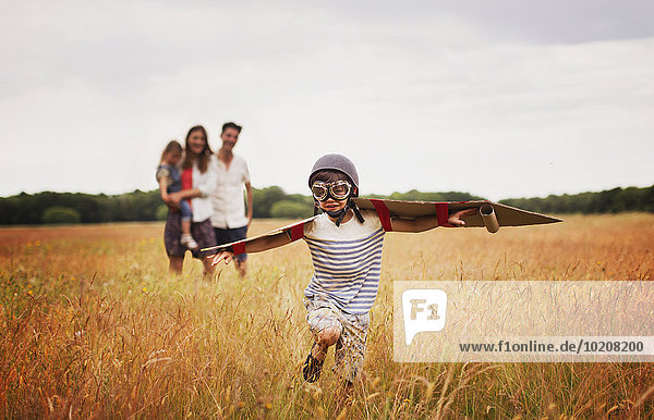 Verspielter Junge mit Flügeln in Fliegermütze und Fliegerbrille im Feld