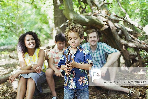 Familie beobachtet Jungen spielen mit Stöcken im Wald