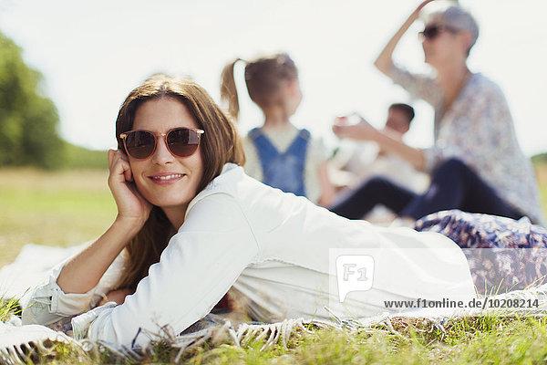 Portrait lächelnde Frau auf Decke im sonnigen Feld liegend