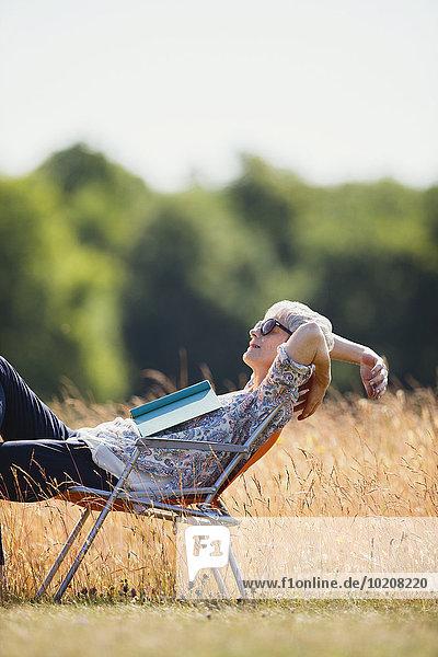 Sorglose Seniorin entspannt mit Buch im sonnigen Feld