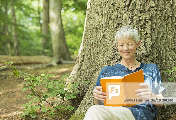 Lächelnde Seniorin liest Buch gegen Baum im Wald