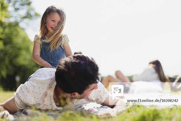 Verspielte Tochter auf Vater im sonnigen Feld