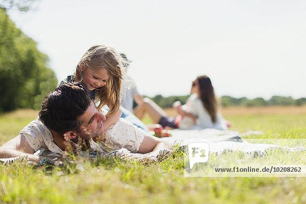 Zärtliche Tochter auf dem Vater im sonnigen Feld liegend