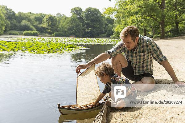 Vater und Sohn spielen mit Spielzeug-Segelboot am Seeufer