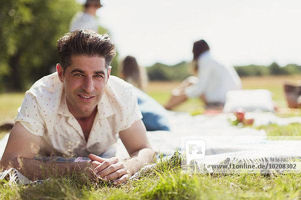 Portrait lächelnder Mann auf Picknickdecke im sonnigen Feld liegend