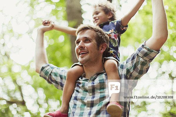 Vater trägt Sohn auf Schultern unter Bäumen