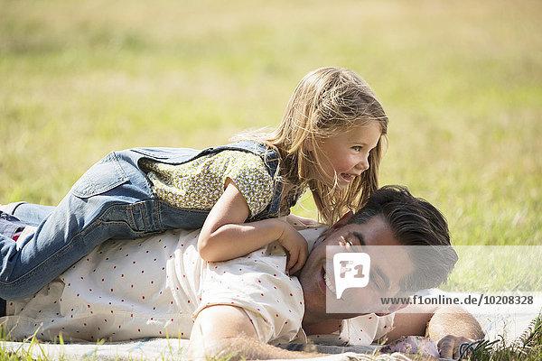 Verspielte Tochter auf dem Vater im sonnigen Feld liegend