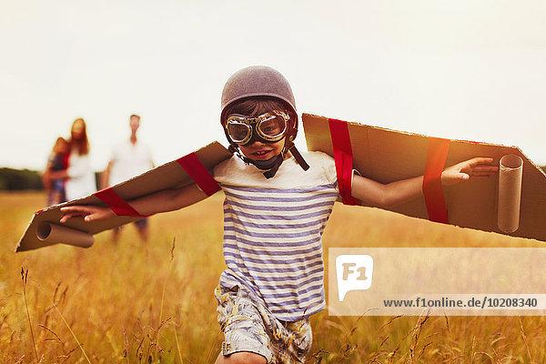 Junge mit Flügeln in Fliegermütze und Fliegerbrille im Feld