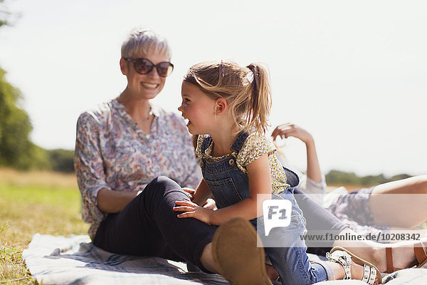 Großmutter und Enkelin lachend auf Decke im sonnigen Feld