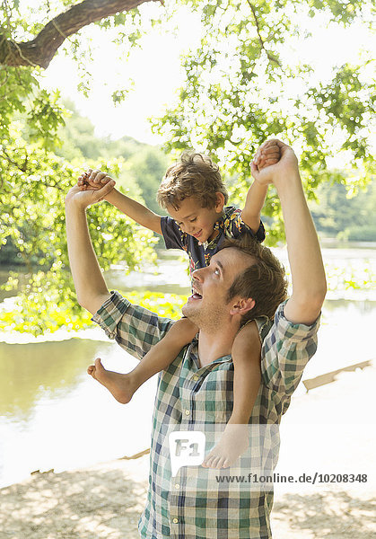 Verspielter Vater mit Sohn auf den Schultern am Seeufer