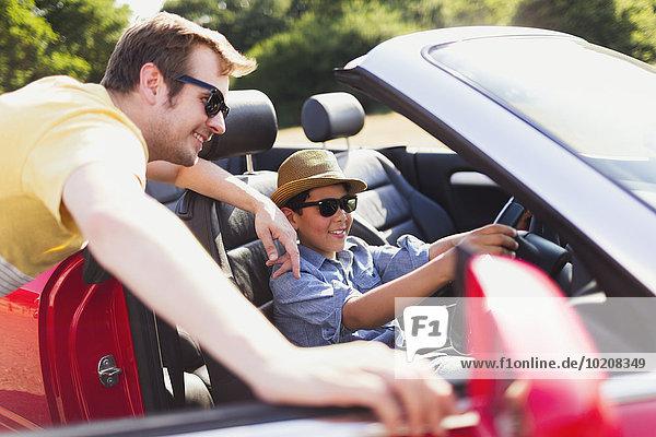Vater beobachtet Sohn, der vorgibt, im Cabrio zu fahren.