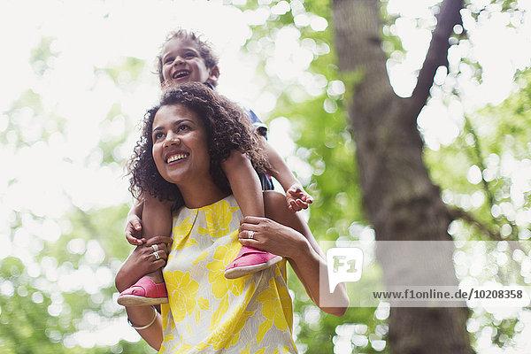 Lächelnde Mutter mit Sohn auf den Schultern unter dem Baum